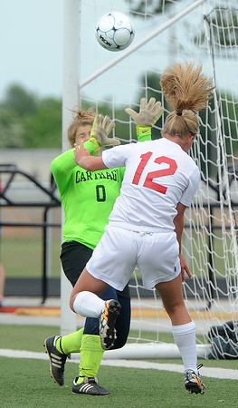 Carl Junction's Kira Wentworth tries to head the ball past Carthage goal keeper Emily Edmonson during their game on Tuesday night at Webb City.<br /> Globe | Laurie Sisk