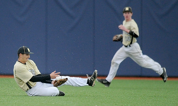 Neosho centerfielder Clint Winchester makes a diving catch as teammate Kaleb Moreland backs up the play during the Wildcats' Class 5, District 12 semifinal game against Carthage on Tuesday at JHS.<br /> Globe | Laurie Sisk