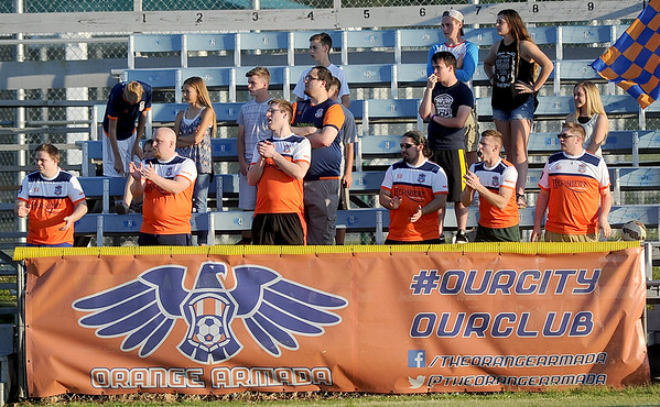 Members of the small but rowdy Orange Armada cheer on their Joplin Demize soccer team during their match against Fort Worth on Saturday night at Hershewe Field.<br /> Globe | Laurie Sisk