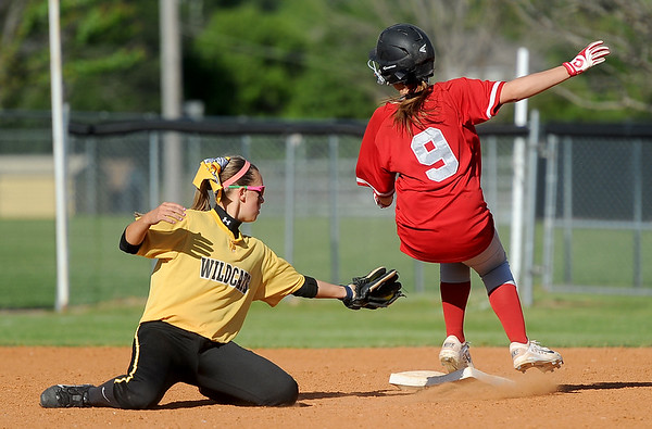 Liberal's Callie Cornell slips past Diamond shortstop Whitney DeGonia after a passed ball during their Class1, District 11 championship game on Wednesday at Diamond.<br /> Globe | Laurie SIsk