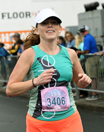 Jenna Mutz, of Joplin, smiles as she crosses the finish line with the top time in the women's half marathon on Saturday at the Joplin Memorial Marathon.<br /> Globe | Laurie SIsk