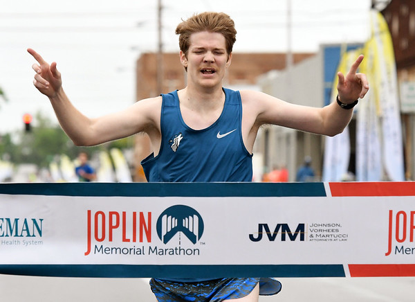 Josiah Coen, of Carthage, crosses the finish line with the top time in the men's 5K on Saturday at the Joplin Memorial Marathon.<br /> Globe | Laurie SIsk