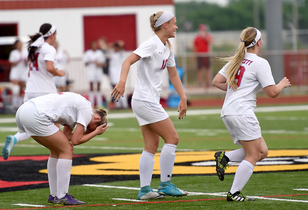 From the left: Webb City sophomore Allison Cundy is overcome with emotion after a first period goal during the Cardinals' District 12 championship game against Neosho on Wednesday at Cardinal Stadium. Also pictured are teammates Lily Spikereit and McKenzie Brown.<br /> Globe | Laurie SIsk