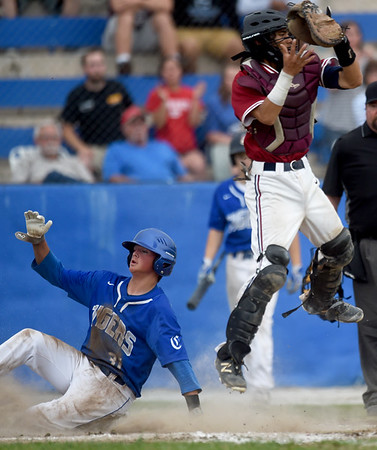 Joplin catcher Luke Benfield leaps for a high throw as Carthage's Kaden Kralicek slides safely home  during their Class 5 District 12 championship game on Tuesday night at Carthage's Carl Lewton Stadium.<br /> Globe | Laurie Sisk