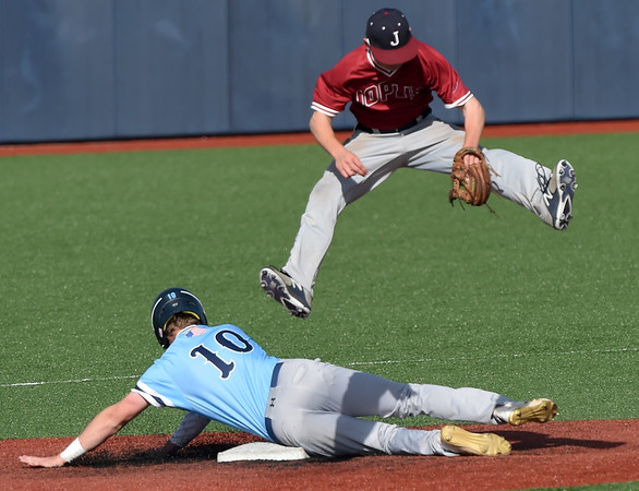 Joplin's Cade Carlson tries to avoid a collision after leaping for an errant throw as Har Ber's Blake Adams slides into second base during their game on Thursday at JHS.<br /> Globe   Laurie Sisk