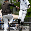 Crowder's Kobe Morris gets a high five from third base coah Kyle Williams after hitting a second-inning grand slam during the Roughriders game against Mineral Area on Friday at Joe Becker.<br /> Globe | Laurie Sisk