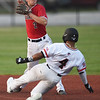 Outlaws' Mike Million (4) gets caught on the front side of an inning ending double play as Nationals shortstop XX XX (2) throws to first base during their game on Friday night at Joe Becker Stadium.<br /> Globe | Laurie Sisk