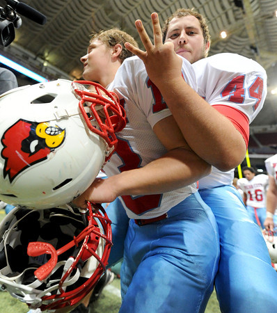Breckin Williams, 13, and Logan Sperry, 44, celebrate the third Webb City Cardinals Class 4 Missouri football championship win at the Edward Jones Dome in St. Louis on Nov. 24, 2012.<br /> Globe/T. Rob Brown