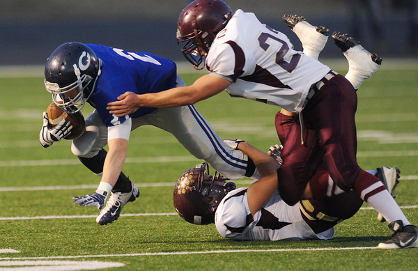Globe/Roger Nomer<br /> Colgan's Colton Gilbert is tackled by Silver Lake's Cody Renfro (bottom) and Caleb Kern during Friday's game.