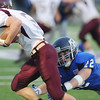 Globe/Roger Nomer<br /> Colgan's Christian Cedeno goes low to tackle Silver Lake's Cody Renfro during Friday's game.