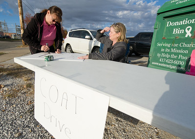 From the left: Missouri Southern Social Work students Evie Cotten and Lisha Reynolds prepare signs to draw attention to their coat drive on Friday at Watered Gardens. As of Friday more than 165 coats had been collected. Persons wishing to donate coats or aother winter apparel may email Cotten at cottene@mymail.mssu.edu. Globe | Laurie Sisk