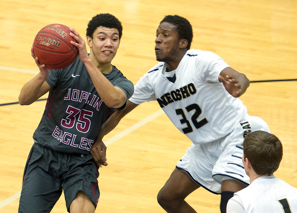 Joplin's Dineji Olaniyan  (35) tries to get past Neosho's Brian Banks (32) and Connor Johnson (1)  during their semifinal game of the Carthage High School Invitational on Friday night at CHS.<br /> Globe | Laurie Sisk