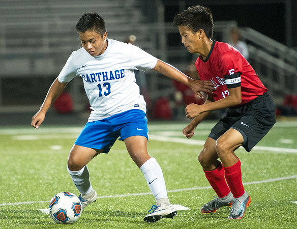 Carthage forward Elder Reyes (13) tries to get past Carl Junction's Aaron Skiles (17) during their match on Tuesday night at Carthage.<br /> Globe | Laurie Sisk