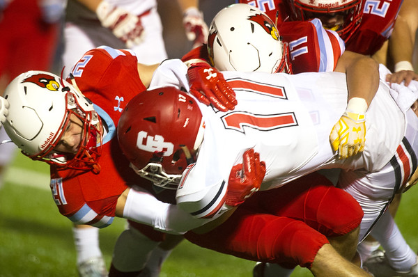 Webb City's Ethan Hilgendorf (21) and Seth Thompson (11) work to bring down Carl Junction's Gavin Gannaway (17) during their playoff game on Friday night at Webb City.<br /> Globe | Laurie Sisk