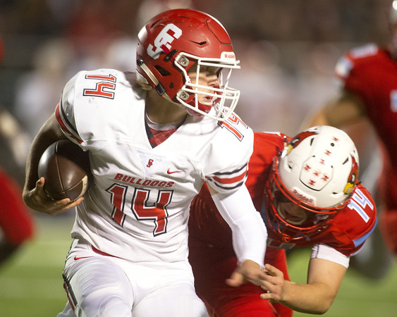 Carl Junction quarterback Joe Kennedy (14) tries to get past Webb City linebacker Cade Beason (14)  during their playoff game on Friday night at Webb City.<br /> Globe | Laurie Sisk