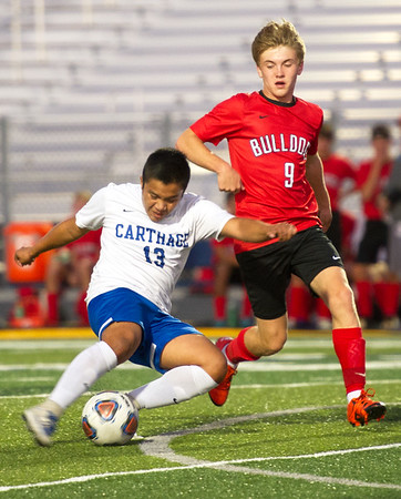 Carthage forward Elder Reyes (13) gets a shot off as past Carl Junction's Kolby Nace (9) defends during their match on Tuesday night at Carthage.<br /> Globe | Laurie Sisk