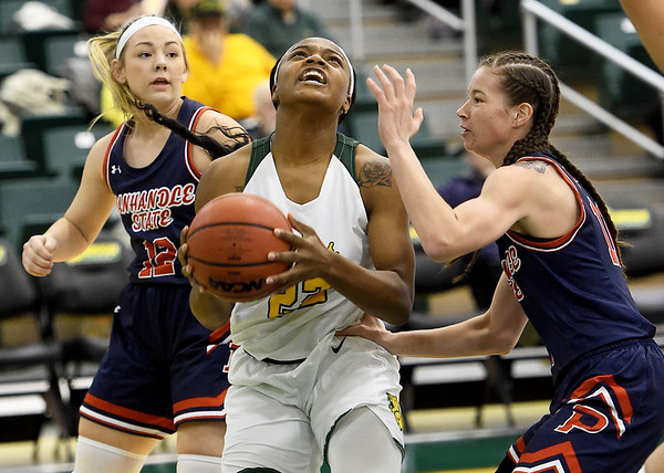 Missouri Southern's Chasidee Owens (22) splits Panhandle State defenders Monti Regier (12) and Hannah Faulks (11) during their game on Tuesday night at Leggett & Platt.<br /> Globe | Laurie Sisk
