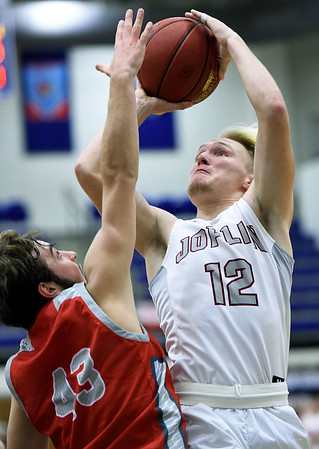 Joplin's Blake Tash (12) shoots over Joplin's Zach Westmoreland (32) challenges West Plains' Allen Marcak (43) during their semifinal game in the Carthage Invitational on Friday night at CHS.<br /> Globe | Laurie Sisk