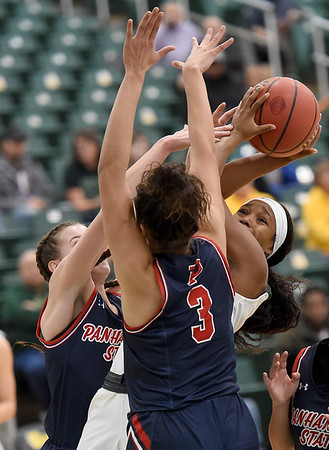 Missouri Southern's Chasidee Owens (22) splits Panhandle State defenders Hannah Faulks, left, and Kim Best (3) during their game on Tuesday night at Leggett & Platt.<br /> Globe | Laurie Sisk