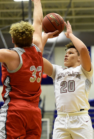 Joplin's Isaiah Davis (20) shoots over West Plains' Garrett Warren (33) during their semifinal game in the Carthage Invitational on Friday night at CHS.<br /> Globe | Laurie Sisk