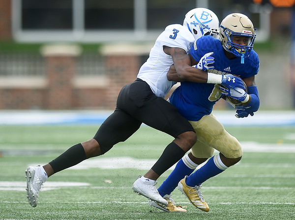 Northeastern A&M's Marcheenan Hair (8) tries to break the grasp of Blinn's Darius Milton (3) during their game on Saturday afternoon at NEO.<br /> Globe | Laurie Sisk
