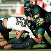 Missouri Southern's Elden Titania, bottom, pulls down Emporia State's Carlos Grace (22) as Colton Winder assists on the tackle during their game on Saturday at Fred G. Hughes Stadium. <br /> Globe | Laurie Sisk