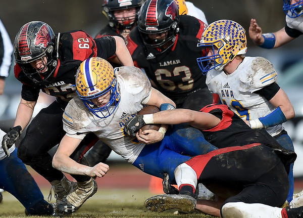 Lamar linebacker Trace Willhite, right, tries to strip the ball from Ava quarterback Nate Swofford during their playoff game on Saturday at Lamar. Also pictured: Lmar's Robert Lawrence (62), Juan Juarez (63) and Ava's Josh Bray (19).<br /> Globe | Laurie Sisk