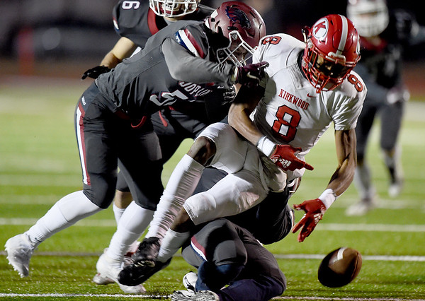 Joplin's Will Boman (51) and James Matou (14) force a fumble by Kirkwood's Will Lee (8) during their playoff game on Friday night at Junge Stadium.<br /> Globe | Laurie Sisk
