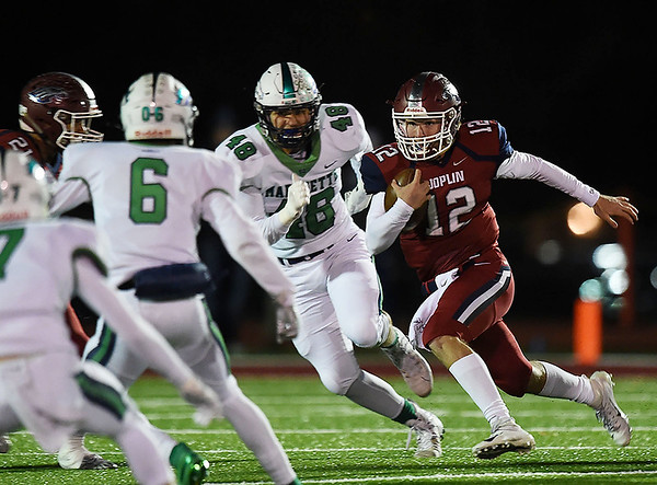 Joplin quarterback Blake Tash (12) gets past Marquette's Josh Merz (48) during their Class 6 District 3 Championship game on Friday night at Junge Stadium.<br /> Globe | Laurie SIsk