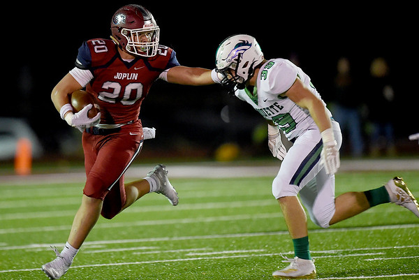 Joplin's Isaiah Davis (20) gets past Marquette's Matt KAdlec (39) during their Class 6 District 3 Championship game on Friday night at Junge Stadium.<br /> Globe | Laurie SIsk