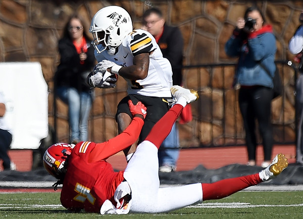 Pittsburg State's William Bazzle (4) tries to bring down Missouri Western's Shamar Griffith (3) during their game on Saturday at PSU.<br /> Globe | Laurie Sisk