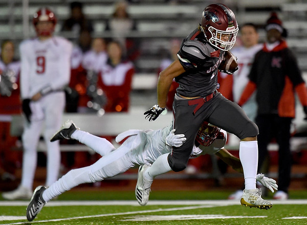 Joplin's Zach Westmoreland (1) breaks the tackle of Kirkwood's Jackson Fortner (6) for a long touchdown reception during their playoff game on Friday night at Junge Stadium.<br /> Globe | Laurie Sisk