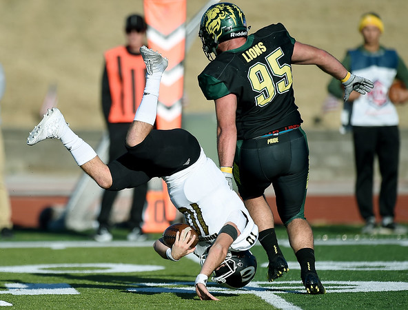 Emporia State quarterback Braden Gleason (10) goes heels-over-head into Missouri Southern's Levi Marlay (95) after beibg tripped up by Colton Winder during their game on Saturday at Fred G. Hughes Stadium. <br /> Globe | Laurie Sisk