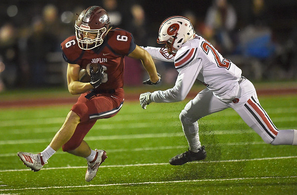 Joplin's Nathan Glades (6) gets past Jefferson City's Steven Samuels (21) for a long gain during their district play off game on Friday night at Junge Stadium.<br /> Globe | Laurie Sisk