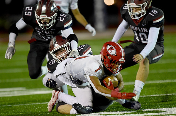Joplin defenders Elijah Eminger (29,) Marcelino Puente (49) and Scott Lowe (18) bring down Kirkwood's Cole Johnson (1) during their playoff game on Friday night at Junge Stadium.<br /> Globe | Laurie Sisk