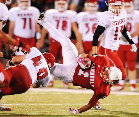 Globe/T. Rob Brown<br /> Webb City's Phoenix Johnson flies through the air while getting brought down by Ozark's Ian Reese Friday night, Oct. 12, 2012, at Webb City's field.