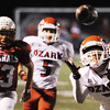 The Joplin Globe/T. Rob Brown<br /> Ozark's David Salazar (7) reaches out for the ball as teammate Levi Barnes (5) and Webb City defender Landon Baker (83) move toward the play Friday night, Oct. 12, 2012, at Webb City's field.