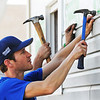NASCAR driver Kasey Kahne helps Rebuild Joplin and Farmers Insurance volunteers put siding on a home Wednesday, Oct. 2, 2013, in the tornado zone.<br /> Globe | T. Rob Brown