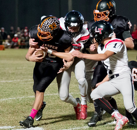 Globe/Israel Perez<br /> Jasper's Blake Feffries (33) is tackled by Lockwood's Ben Schnelle (10) and Paxton Masterson (1) as teammate Nick Adkins (14) looks on during Friday's game in Jasper.