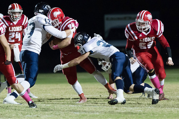 Globe/Israel Perez<br /> Baxter Springs' Doug Dardenne (34) is tackled by Galena's Kyle Martin (13) and Gavin Nowlin (21) during Friday's game in Baxter Springs.
