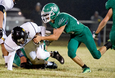 Quapaw's Austin Thomasson (25) tries to strip the ball from Hurlbert's Dae'Qwan Leathers (5) during their game on Thursday night at Quapaw. Globe | Laurie Sisk