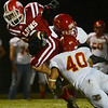 Globe/Roger Nomer<br /> Columbus' Alex Crouch and Zach Porter tackle Baxter Springs' Donovan Anderson during Friday's game in Baxter Springs.
