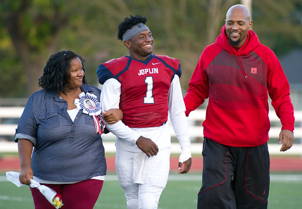 Joplin quarterback Jokiem Crawford smiles at his father, Joey Crawford, during Senior Night on Friday night at Junge Field. Also pictured is Jokiem's mother, Kim Sparks.<br /> Globe | Laurie SIsk