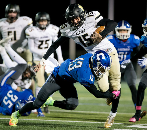Globe Israel Perez<br /> Neosho's Gavin Kelly (15) carries the ball as he gets tackle by Corben Pugh (13) of Carthage during the Class 5 District 5 semifinal on Friday night at David Haffner Stadium in Carthage.