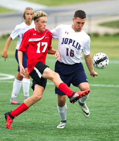 Joplin senior defender Liam Clevenger (16) and West Plains midfielder Nate Thomas (17) vie for the ball during their match on Tuesday night at JHS.<br /> Globe | Laurie Sisk