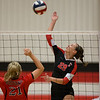 Carl Junction's Grace Southern (29) spikes the ball as Madison Hall (21) of McDonald Co. tries to make a block during their Class 4 District 12 tournament at Carl Junction High School