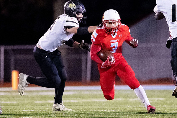 Cardinal's Sergio Perez (3) runs the ball as he gets past the tackle of Drew Osborn (13) of Neosho catches during their Class 4 District 6 Championship game on Friday night at Cardinal Stadium.<br /> Globe Israel Perez