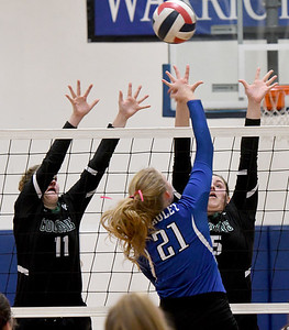 College Heights blockers Olivia Rogers (11) and Riley Chafee (15) challenge a spike by McAuley's Claire Lowry (21) during their match on Tuesday night at McAuley. Globe | Laurie Sisk