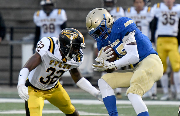 Northeastern A&M running back Darran Williams (25) works to get past Tyler Junior College's LaDarian Hudson (32) on Saturday at NEO.<br /> Globe | Laurie SIsk