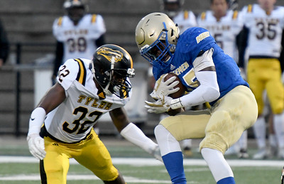 Northeastern A&M running back Darran Williams (25) works to get past Tyler Junior College's LaDarian Hudson (32) on Saturday at NEO. Globe | Laurie SIsk